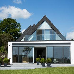 Idéer för att renovera ett mellanstort funkis vitt stenhus, med två våningar och valmat tak