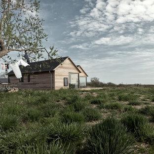 Ejemplo de fachada de casa beige, escandinava, de una planta, con revestimiento de madera y tejado a dos aguas