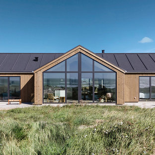 Imagen de fachada de casa marrón, nórdica, de tamaño medio, de una planta, con revestimiento de madera, tejado a dos aguas y tejado de varios materiales