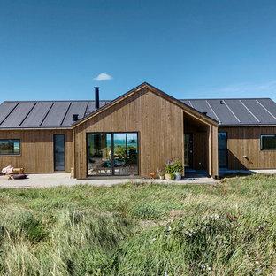 Foto de fachada de casa marrón, nórdica, de tamaño medio, de una planta, con revestimiento de madera, tejado a dos aguas y tejado de varios materiales