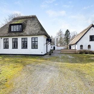 Inredning av ett lantligt vitt hus, med två våningar, sadeltak och levande tak