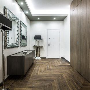 Idee per un corridoio design con pareti bianche, parquet scuro, una porta bianca, una porta singola e pavimento marrone
