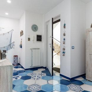 Inspiration för mellanstora medelhavsstil foajéer, med vita väggar, klinkergolv i porslin och turkost golv