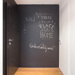 На фото: фойе в стиле шебби-шик с серыми стенами, паркетным полом среднего тона и черной входной дверью с