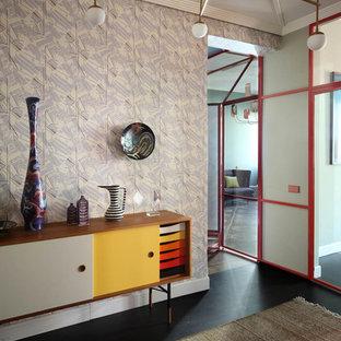 Esempio di un ingresso minimalista con pareti beige, pavimento nero e una porta rossa
