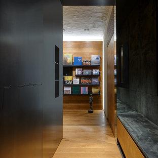 Стильный дизайн: коридор в современном стиле с черными стенами, паркетным полом среднего тона и коричневым полом - последний тренд