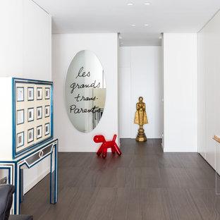 Ispirazione per un ingresso o corridoio contemporaneo con pareti bianche e pavimento grigio