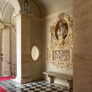 Esempio di un ingresso mediterraneo con pareti beige, una porta a due ante, una porta nera e pavimento multicolore