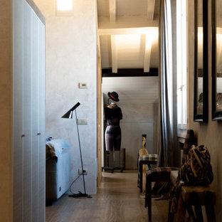 Idées déco pour un couloir éclectique de taille moyenne avec un mur gris, un sol en bois foncé, un sol marron et un plafond en bois.