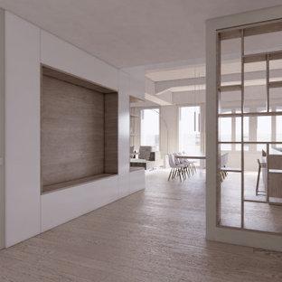 Nordisk inredning av en stor foajé, med grå väggar, mellanmörkt trägolv, en enkeldörr, en vit dörr och brunt golv