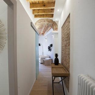 Idee per un corridoio boho chic di medie dimensioni con pareti bianche, parquet chiaro, una porta a pivot, una porta bianca e pavimento beige