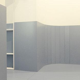 Cette photo montre un petit couloir tendance avec un mur blanc, un sol en carrelage de porcelaine et un sol turquoise.