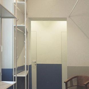 Foto på en liten funkis foajé, med vita väggar, klinkergolv i porslin, en dubbeldörr, mörk trädörr och turkost golv