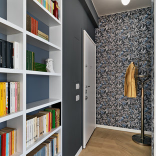 This is an example of a small contemporary entry hall in Milan with grey walls, medium hardwood floors, a single front door, a white front door and brown floor.