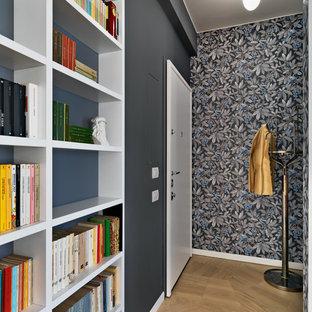 Foto di un piccolo corridoio minimal con pareti grigie, pavimento in legno massello medio, una porta singola, una porta bianca e pavimento marrone