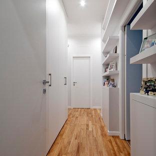 Ispirazione per un ingresso o corridoio minimal con pareti bianche e pavimento in legno massello medio