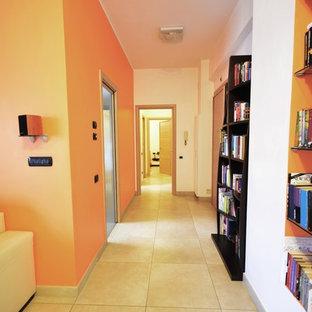 ローマの中サイズのモダンスタイルのおしゃれな廊下 (オレンジの壁、磁器タイルの床、ベージュの床) の写真