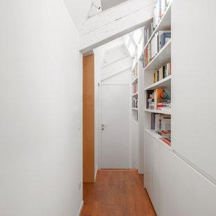 Esempio di un piccolo ingresso o corridoio design con pareti bianche, travi a vista, soffitto a volta, pavimento in legno massello medio e pavimento marrone