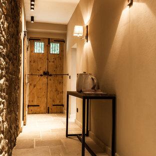 Ispirazione per un corridoio rustico con pareti beige, una porta a due ante e una porta in legno bruno
