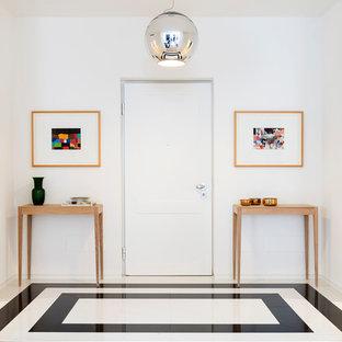 Esempio di un ingresso contemporaneo con pareti bianche, una porta singola, una porta bianca e pavimento multicolore