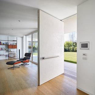 Inspiration för mycket stora moderna foajéer, med vita väggar, ljust trägolv och en vit dörr