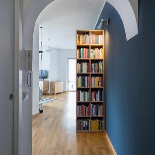 Idee per un piccolo ingresso o corridoio nordico con pareti blu e parquet chiaro