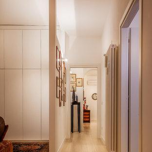 Immagine di un grande ingresso o corridoio contemporaneo con pareti bianche, parquet chiaro e pavimento beige