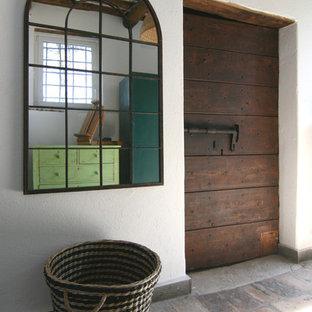 Idee per un piccolo ingresso o corridoio country con pareti bianche, una porta singola e una porta in legno scuro