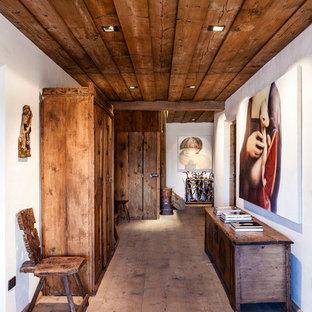 Esempio di un ingresso o corridoio stile rurale di medie dimensioni con pareti bianche e pavimento in legno massello medio