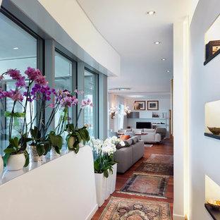 Esempio di un ingresso o corridoio design di medie dimensioni con pareti bianche, pavimento in legno massello medio e pavimento marrone