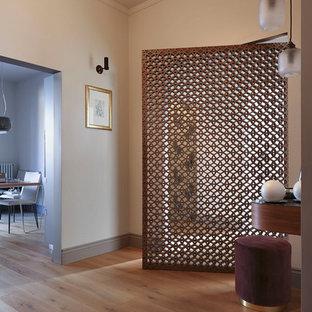 Esempio di un ingresso contemporaneo con pareti beige, parquet chiaro, una porta singola, una porta in metallo e pavimento marrone