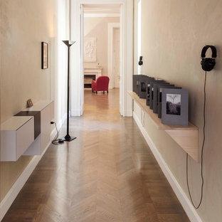 Inspiration för stora moderna hallar, med gula väggar och mellanmörkt trägolv