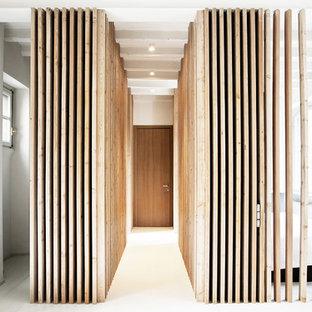 Esempio di un corridoio contemporaneo di medie dimensioni con pareti bianche, una porta singola e una porta in legno bruno
