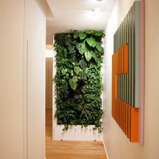 Esempio di un ingresso o corridoio minimal di medie dimensioni con pareti bianche, pavimento marrone e pavimento in legno massello medio