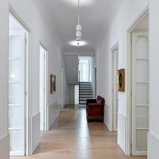 Esempio di un grande ingresso o corridoio design con pareti bianche, parquet chiaro e pavimento beige