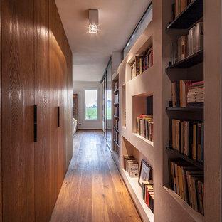 Modelo de recibidores y pasillos contemporáneos con suelo de madera en tonos medios