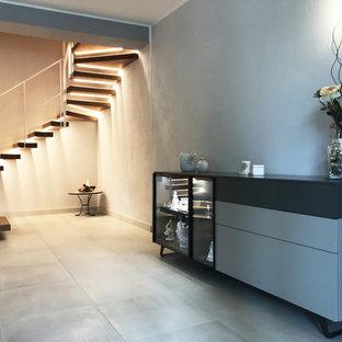 他の地域の中サイズのミッドセンチュリースタイルのおしゃれな廊下 (グレーの壁、磁器タイルの床、マルチカラーの床) の写真