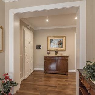 Imagen de distribuidor tradicional con paredes beige, suelo de madera en tonos medios, puerta simple y puerta blanca