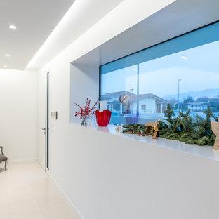 Immagine di un piccolo corridoio design con pareti bianche e una porta bianca