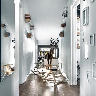 Foto di un ingresso o corridoio nordico di medie dimensioni con pareti bianche, parquet scuro e pavimento marrone
