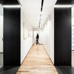 Immagine di un grande ingresso o corridoio minimal con pareti bianche, pavimento in gres porcellanato e pavimento beige