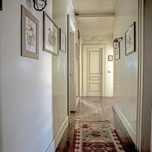 Esempio di un ingresso o corridoio country di medie dimensioni con pareti bianche, parquet scuro e pavimento marrone