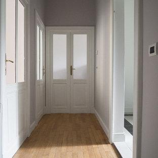他の地域の中くらいのミッドセンチュリースタイルのおしゃれな廊下 (グレーの壁、塗装フローリング、ベージュの床) の写真
