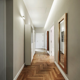 Großer Klassischer Flur mit grüner Wandfarbe, braunem Holzboden und braunem Boden in Rom
