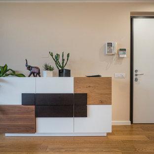 Foto di un grande ingresso o corridoio minimal con parquet chiaro, pareti beige, una porta singola e una porta bianca