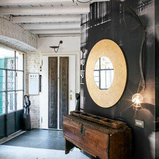 На фото: фойе в стиле лофт с разноцветными стенами, бетонным полом, двустворчатой входной дверью и белой входной дверью с