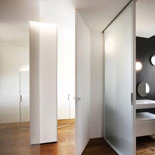 Immagine di un ingresso o corridoio minimal di medie dimensioni con pareti bianche e pavimento in legno massello medio