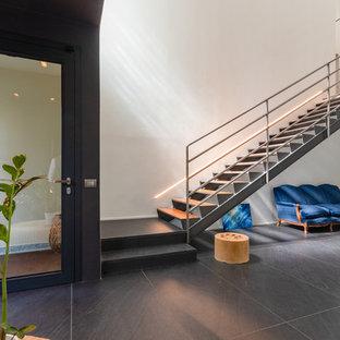 Diseño de distribuidor urbano, grande, con paredes negras, suelo de baldosas de porcelana, puerta simple, puerta metalizada y suelo negro