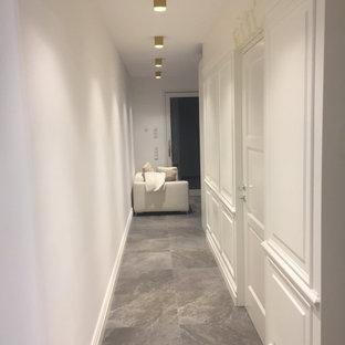 Exempel på en liten skandinavisk hall, med vita väggar, klinkergolv i porslin och grått golv