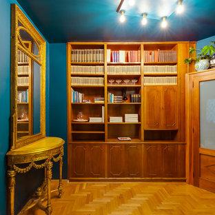 Immagine di un ingresso o corridoio bohémian di medie dimensioni con pareti blu, parquet chiaro, una porta marrone e pavimento marrone